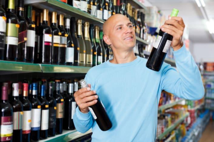 client qui choisit un vin dans un supermarché