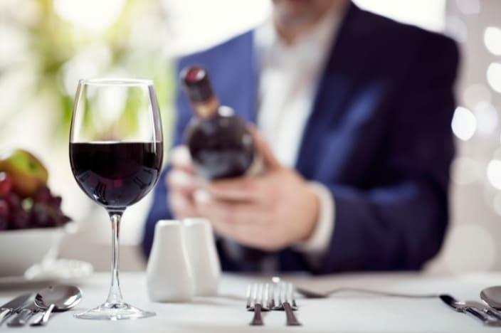homme qui lit une étiquette de vin