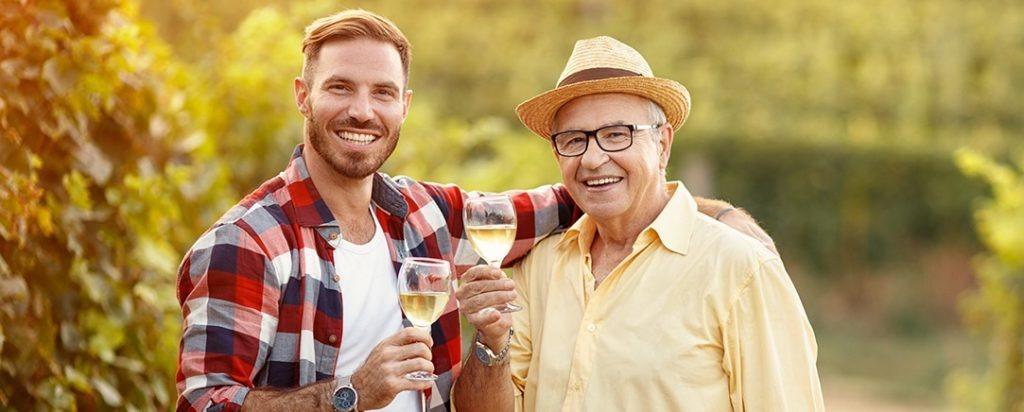 Un père et son fils trinquant un verre de vin à la main à l